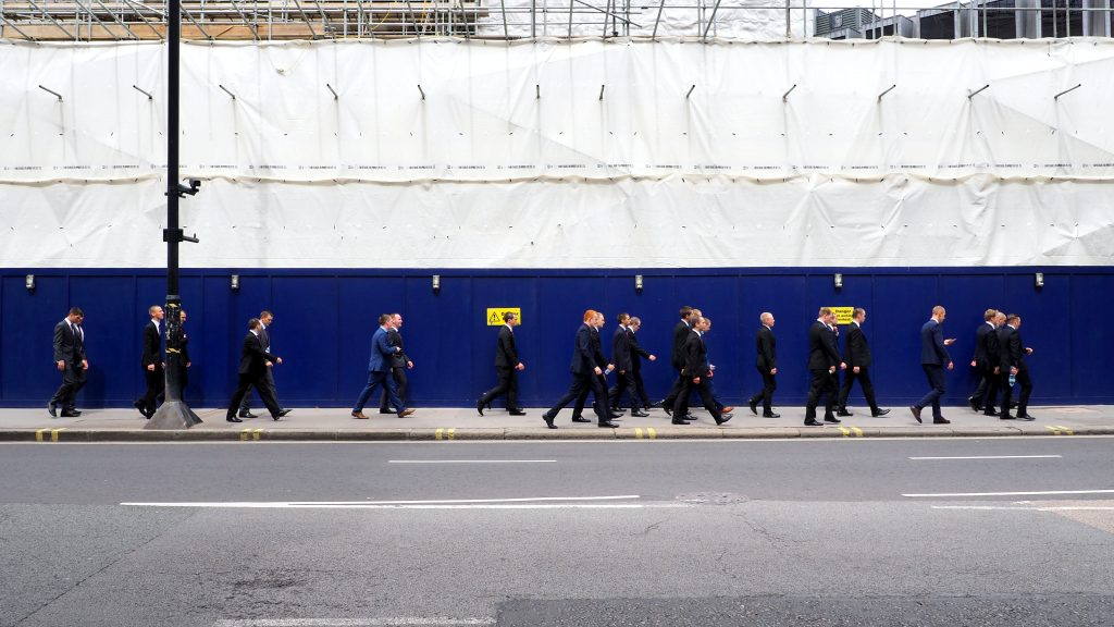 Londoners all suited up in front of a building site.